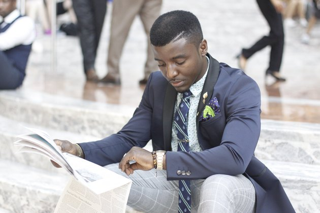 Dapper young Black man reading newspaper and checking watch