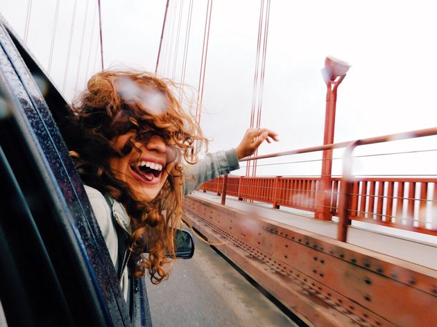 Redheaded woman crossing Golden Gate Bridge in car in the rain