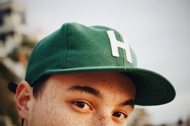 Young person with freckles and a green cap