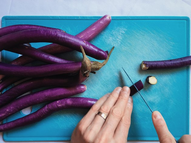 Closeup of hands dicing eggplants