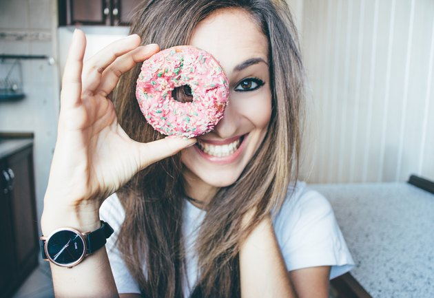 Smiling young woman holds donut over one eye