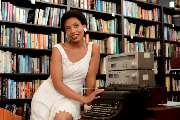 Young Black woman sitting in library with typewriter and old equipment