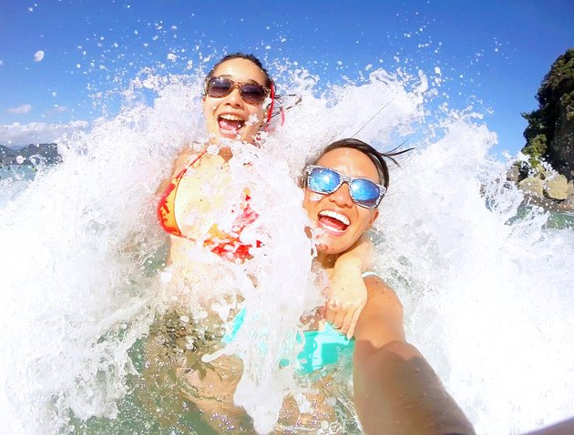 Two happy young people take a selfie as they're hit by a wave on the beach