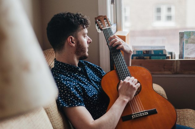 Young white man playing acoustic guitar on couch