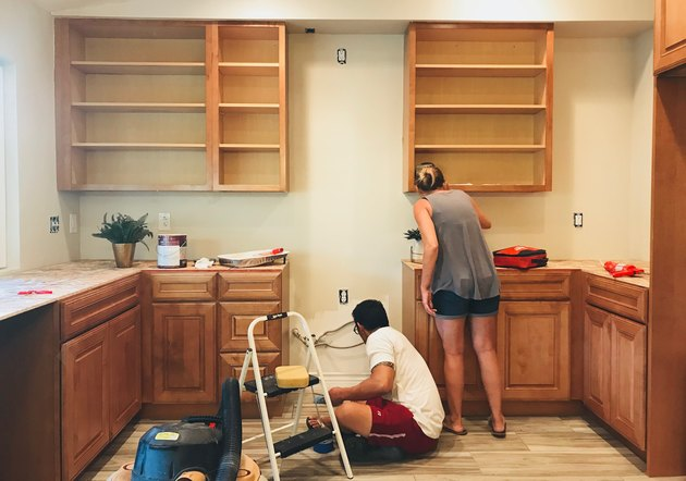 Man and woman doing home repairs on kitchen