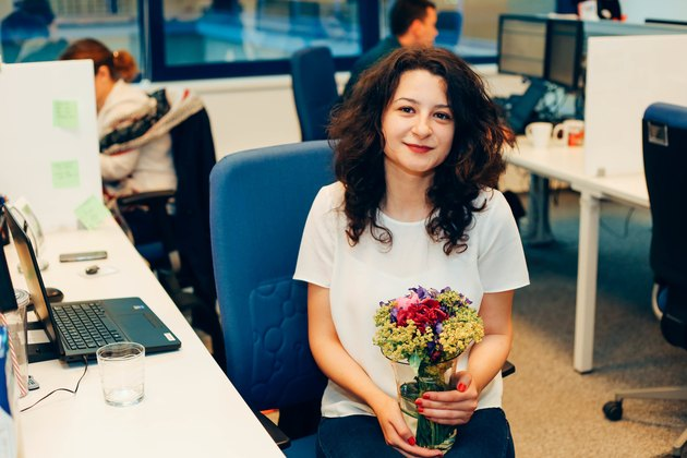 White woman at the office holding a vase of flowers