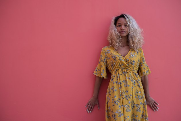 Young Woman of color in yellow dress against raspberry wall