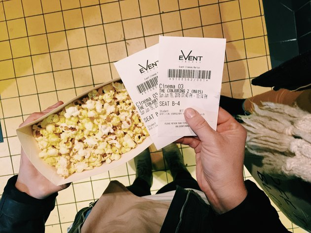 Hands holding popcorn and two movie tickets
