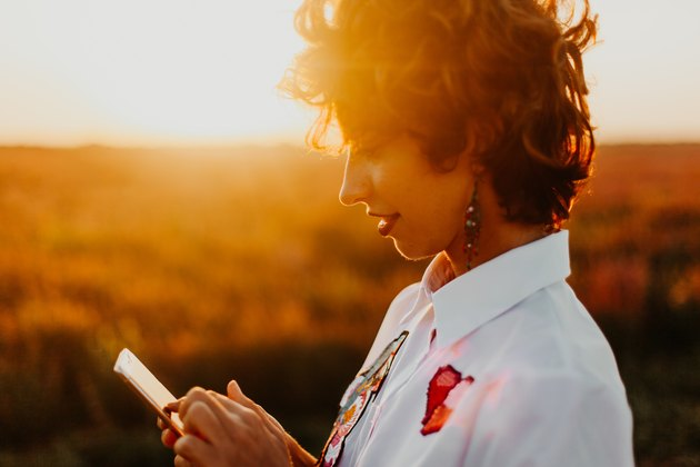 Hip young woman using phone in a sunset field
