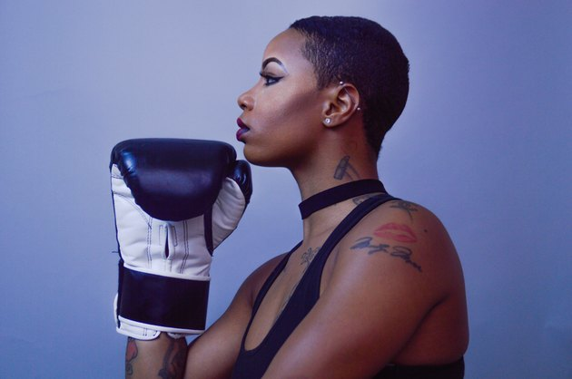 Young Black woman in profile with boxing gloves