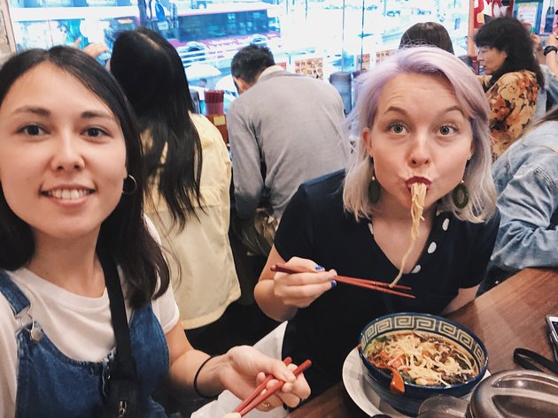 Two women take selfie at ramen shop, one slurping noodles