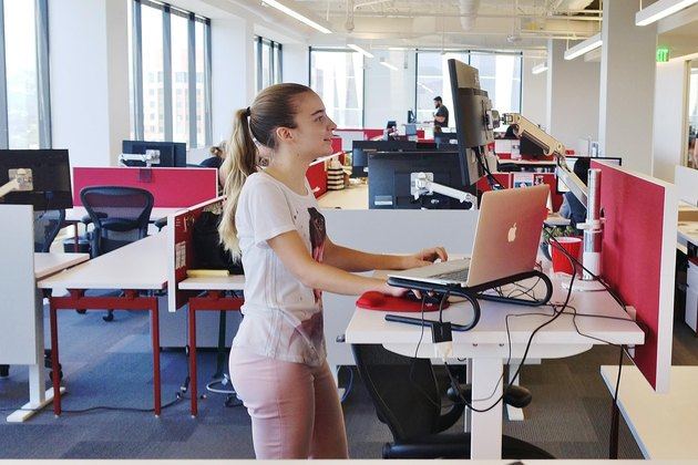 Young woman at standing desk in open-plan office
