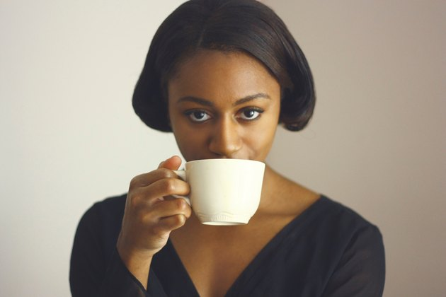 Portrait of fashionable young Black woman drinking coffee from white cup