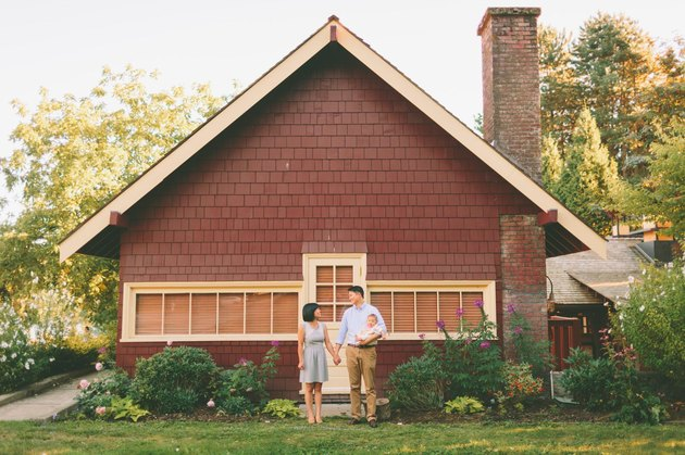 Young couple with baby holding hands in front of new house