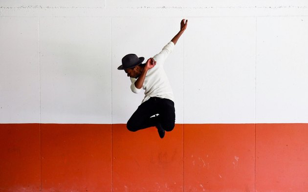 Young Black man leaping in front of white and red wall