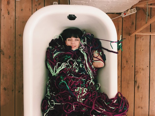 Woman lying in tub covered in yarn