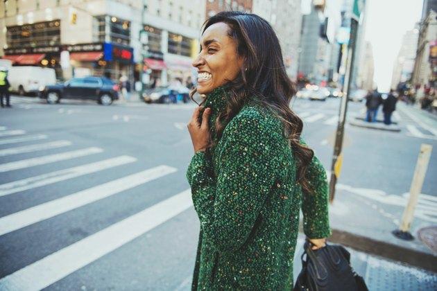 Smiling girl in green coat walking around NYC