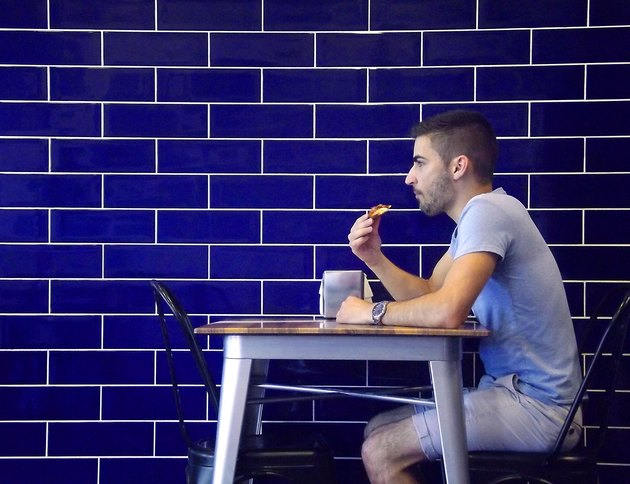 Man eating along against a blue brick wall