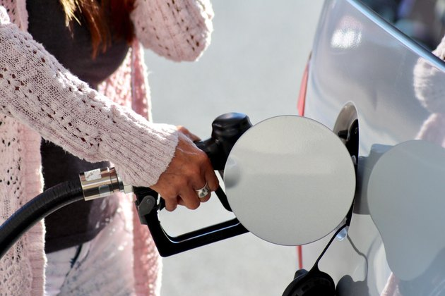 Woman in pink sweater filling up gas tank on white car