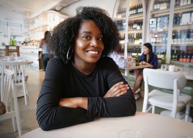 Young Black woman seated at cafe table, smiling confidently