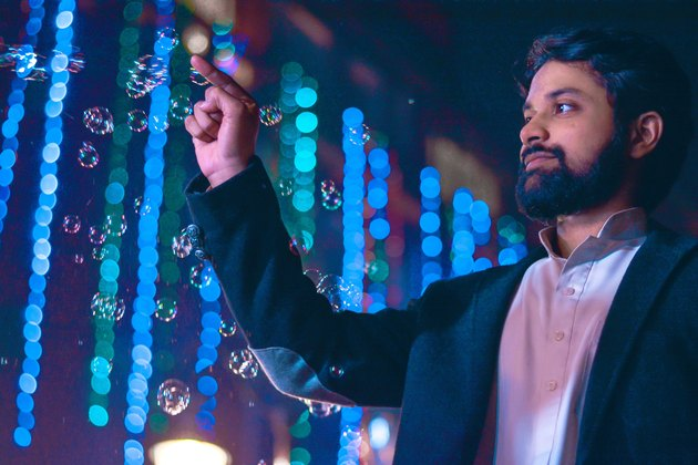 Young South Asian man interacting with strings of lights at night