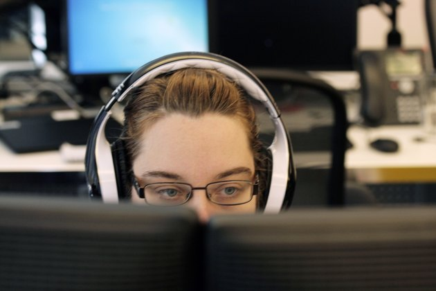 Young white woman wearing headphones at computer station