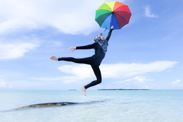 Hijabi leaping above beach holding rainbow umbrella