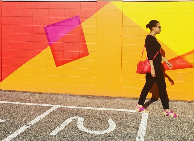 Woman wearing black walking past brightly colored mural