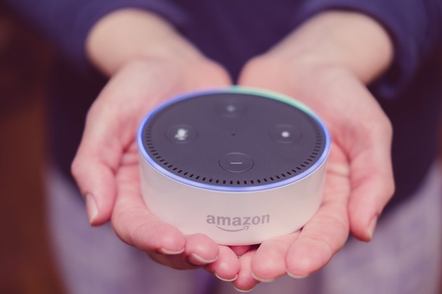Woman holding Amazon Echo Dot in cupped palms