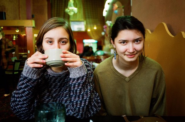 Two young women side by side at cafe