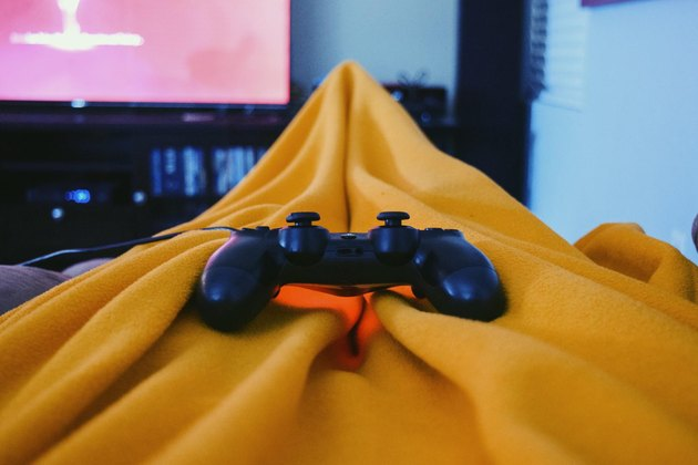 POV holding gaming controls while under yellow fuzzy blanket