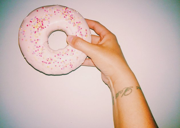 Woman's hand holding pink frosted doughnut with sprinkles