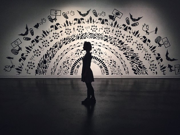 Woman stands in low-lit gallery against monochrome mural