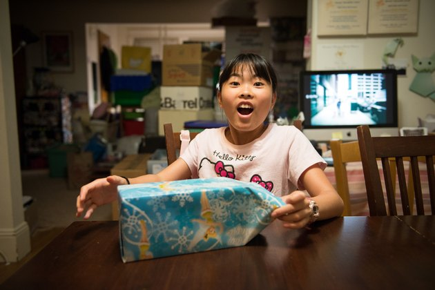 Young Asian girl surprised and delighted at wrapped gift