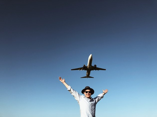 Man doing victory arms with low-flying airplane just above him