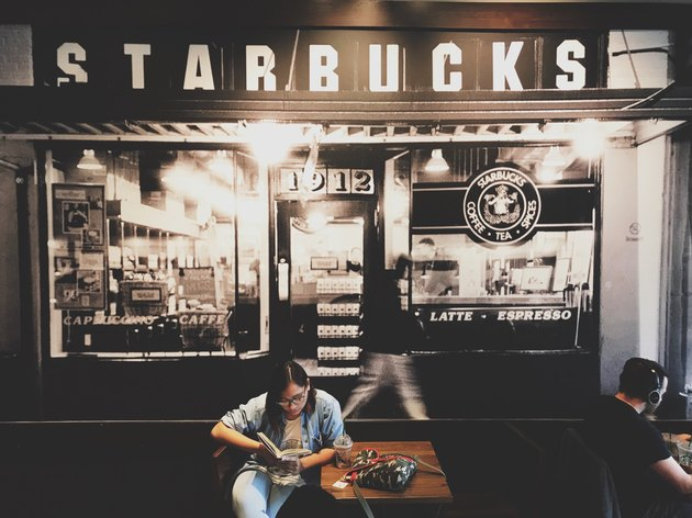 Woman reading inside a Starbucks Cafe