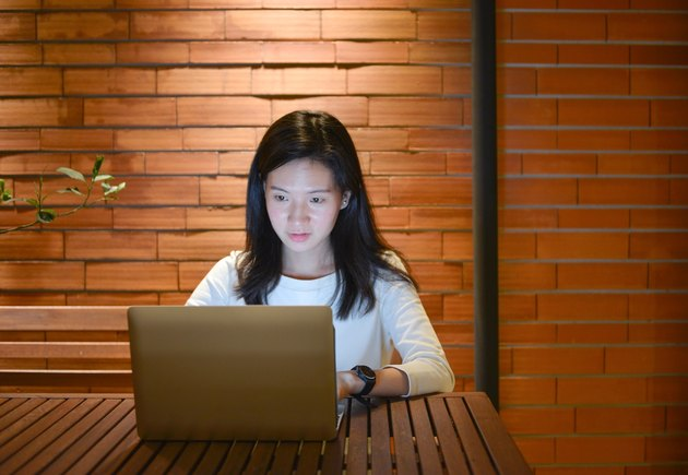Stressed Asian woman using laptop at night, freelance working late