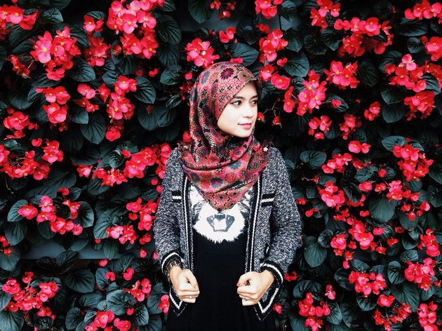 Hijabi smiling in front of garden wall of flowers