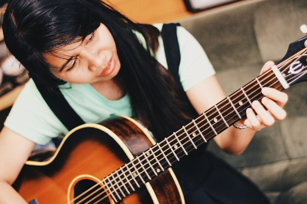 Young woman practices guitar