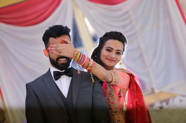 Adorable Indian couple, bridge covering groom's eyes with her hand