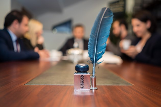 Feather quill and ink in foreground of meeting around large table