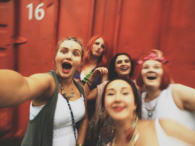 Group of laughing girlfriends taking a group selfie