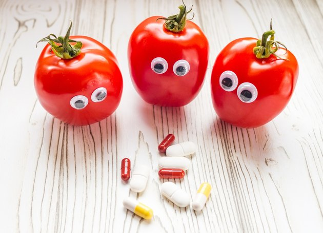 Tomatoes with wobbly eyes looking suspicious at supplements