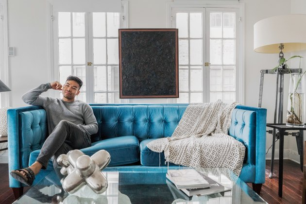 Stylish man on turquoise sofa in sunny loft apartment