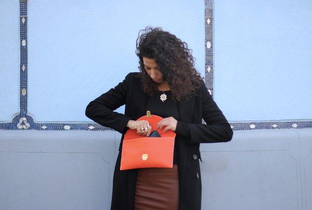 Woman rifling through orange purse