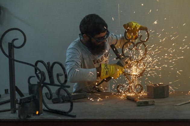 Welder working on ironwork as sparks fly