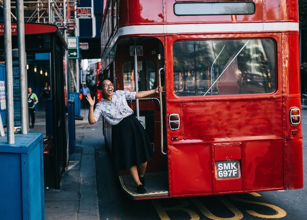 Woman hanging off the back of a London doubledecker bus