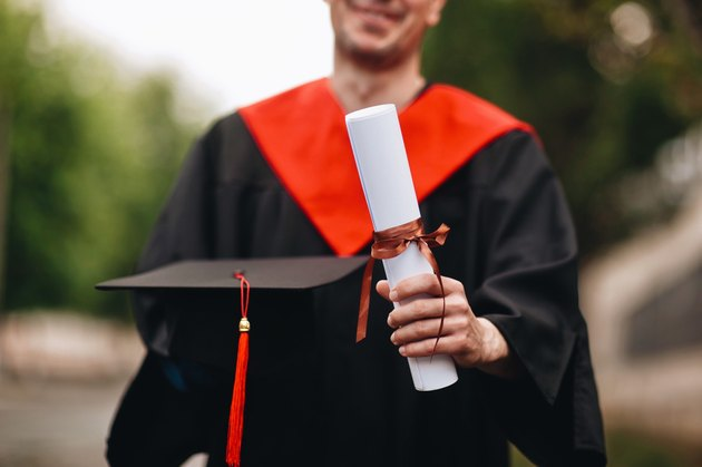 Male college graduate holding rolled-up prop diploma while wearing red and black robes