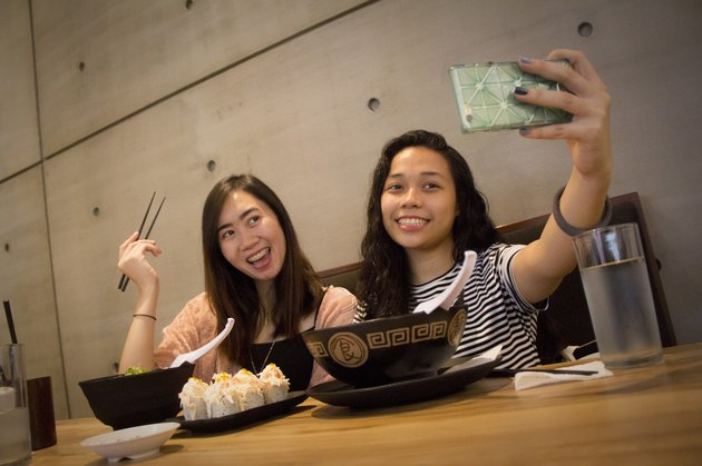 Two young women taking a meal selfie at a ramen joint