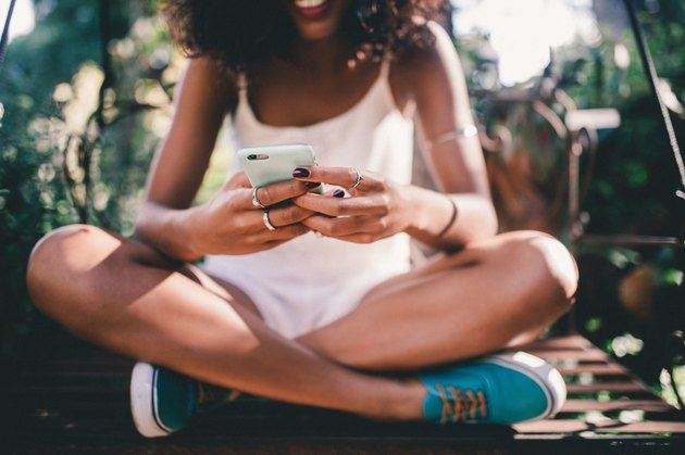 Young Black woman sitting and texting